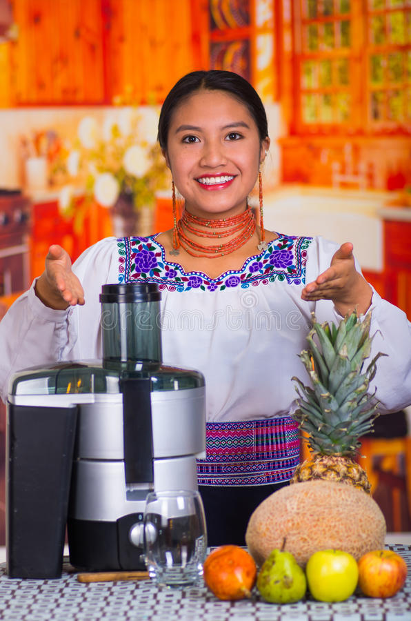 Charming young woman in traditional andean dress standing inside kitchen posing in front of juice maker, healthy royalty free stock images