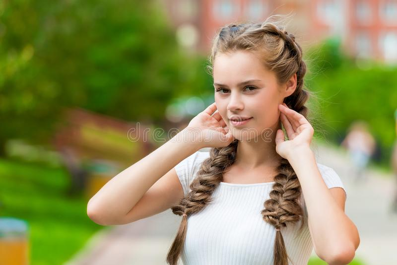 Charming young woman with two braids straightens her hair stock images