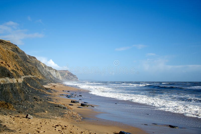 Charmouth海滩风大浪急的海面和金黄盖帽多西特英国 免版税图库摄影