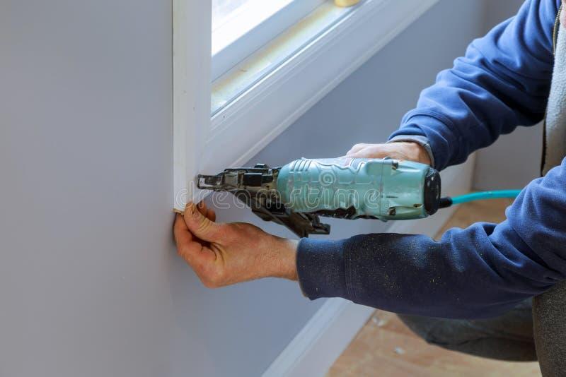 Charpentier à l'aide de l'arme à feu de clou d'air aux bâtis pour la fenêtre, fin sur l'arme à feu de clou photos libres de droits