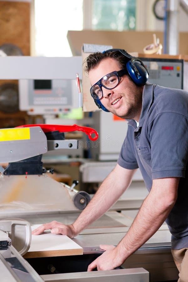 Charpentier à l'aide de la scie électrique photos stock