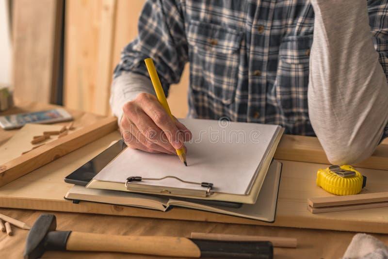 Charpentier écrivant des notes de projet de bloc-notes de presse-papiers et pour faire la liste photo stock