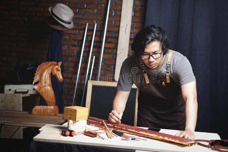 Charpentier asiatique Working dans l'atelier de travail du bois Travailler sur le plan image stock