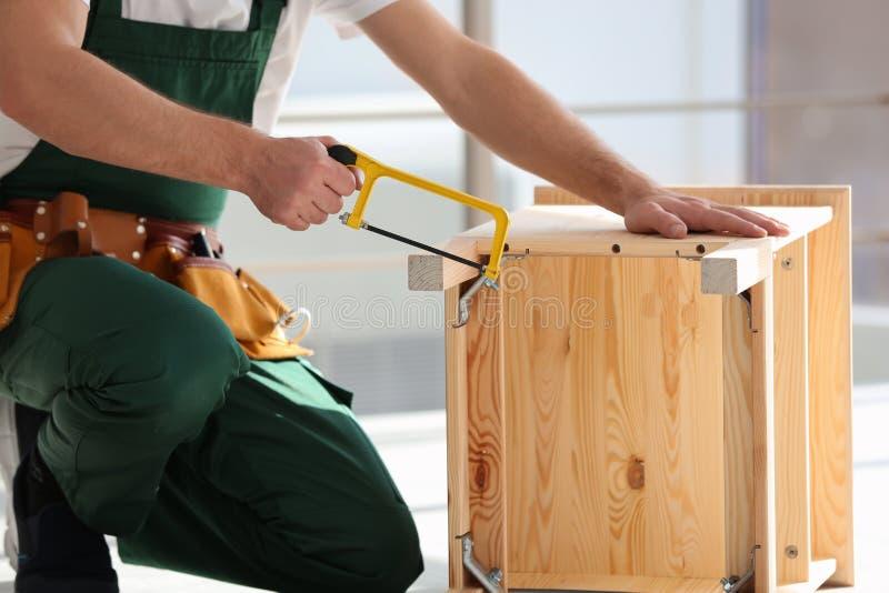 Charpentier dans l'uniforme faisant des meubles à l'intérieur Outils professionnels de construction image stock
