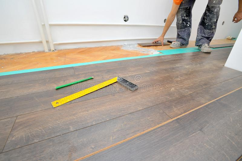 Charpentier effectuant le travail en stratifié de plancher photographie stock