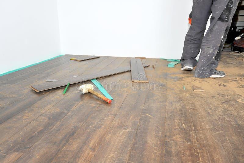 Charpentier effectuant le travail en stratifié de plancher images libres de droits
