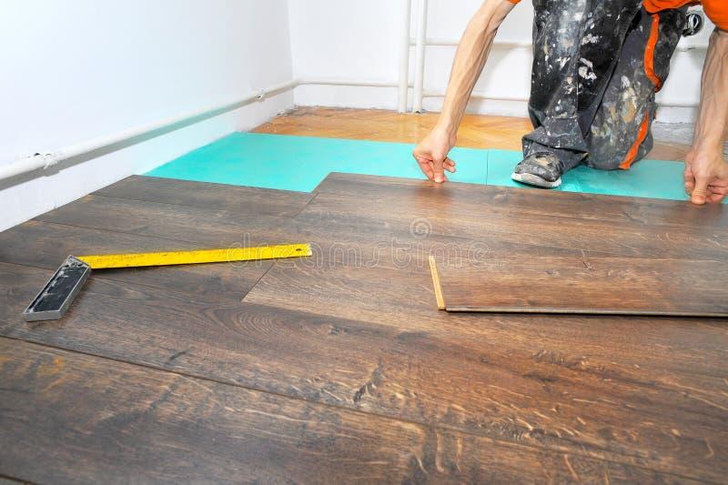 Charpentier effectuant le travail en stratifié de plancher photo libre de droits
