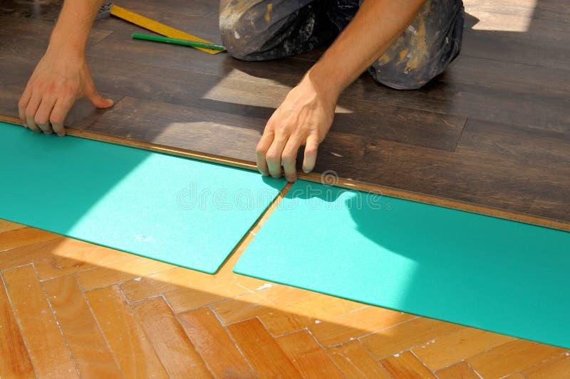 Charpentier effectuant le travail en stratifié de plancher photo stock