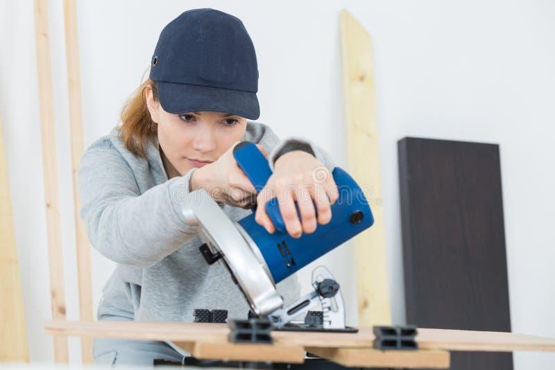Charpentier féminin à l'aide de la machine sur le woodboard images libres de droits