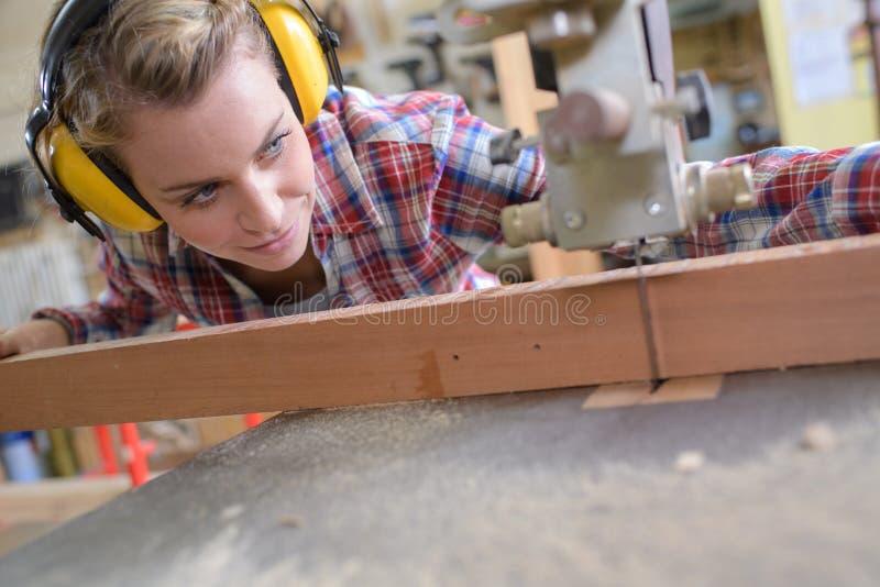 Charpentier féminin coupant la planche en bois image libre de droits