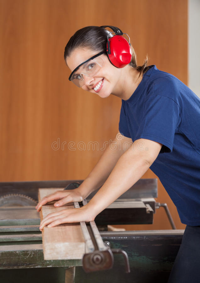Charpentier féminin heureux Using Tablesaw photographie stock