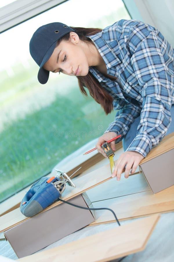 Charpentier f?minin mesurant le conseil en bois appropri? dans l'atelier images stock