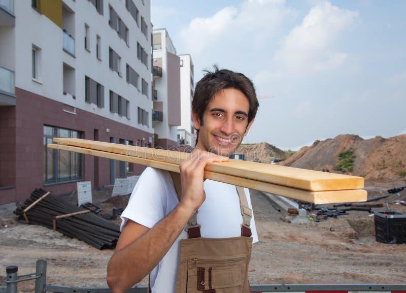Charpentier hispanique riant sur le chantier de construction photographie stock