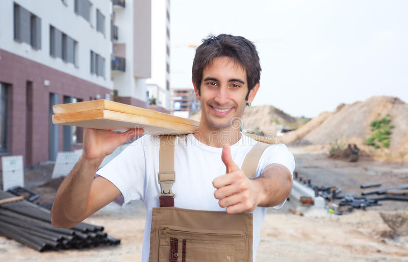 Charpentier hispanique sur le chantier de construction montrant le pouce photographie stock