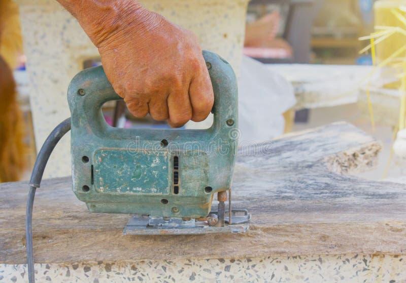 Charpentier ou menuisier travaillant avec la scie électrique - plan rapproché sur des mains, charpentier sur la nature, charpenti photo libre de droits