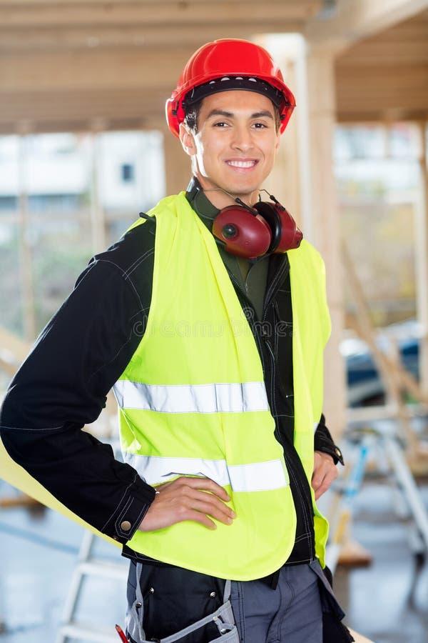 Charpentier Standing With Hands sur des hanches au chantier de construction photographie stock