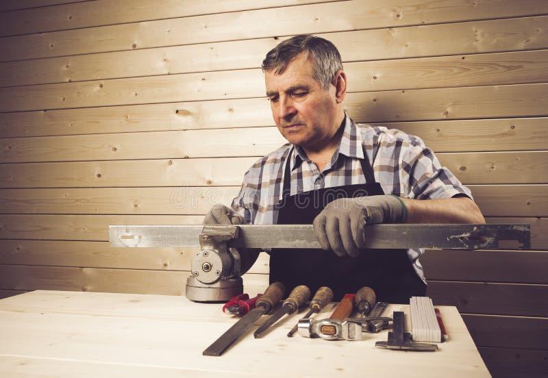 Charpentier supérieur travaillant dans son atelier photos stock
