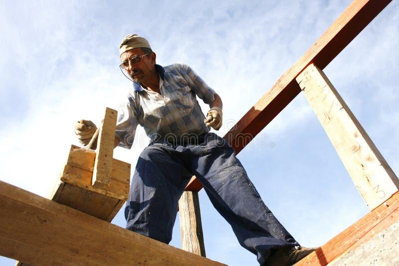 Charpentier travaillant avec des clous et un cadre en bois   photo libre de droits