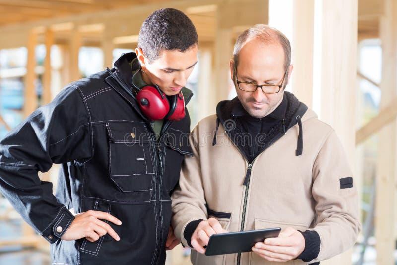 Charpentiers à l'aide du PC de Tablette au site photographie stock libre de droits