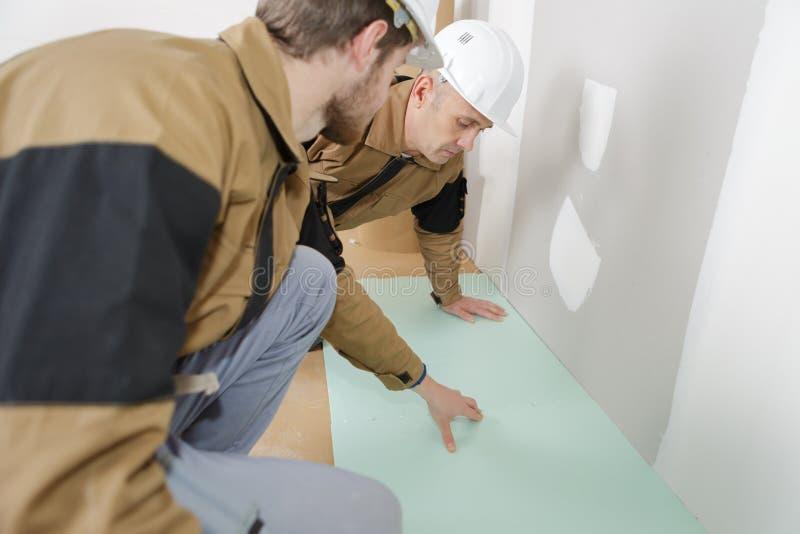Charpentiers effectuant le travail en stratifié de plancher photos stock