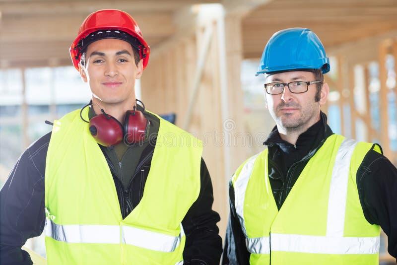 Charpentiers sûrs dans les vêtements de protection au chantier de construction images stock