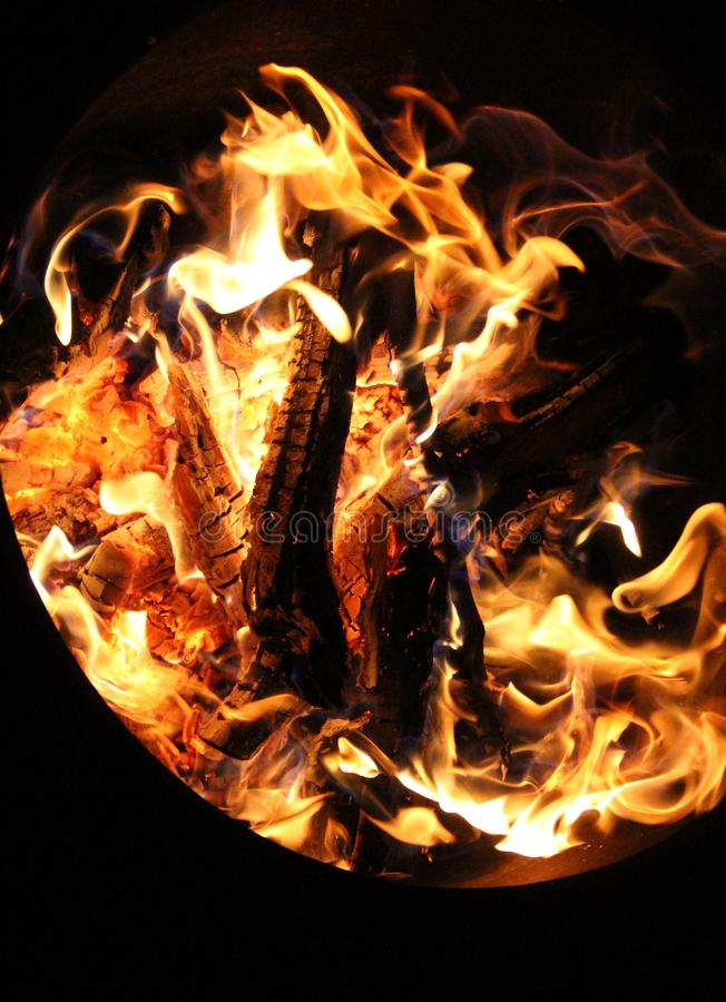 Charred and fire five. Charred wood and bright flames on dark background royalty free stock photo
