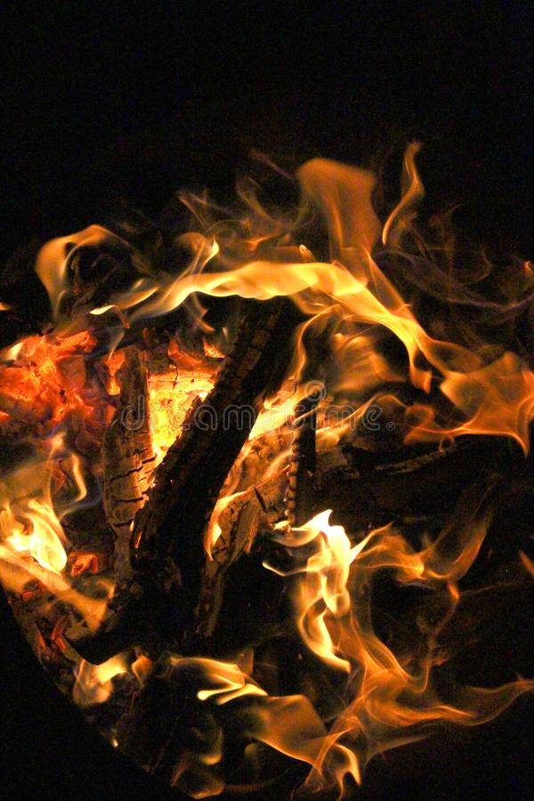Charred and fire four. Charred wood and bright flames on dark background stock photography