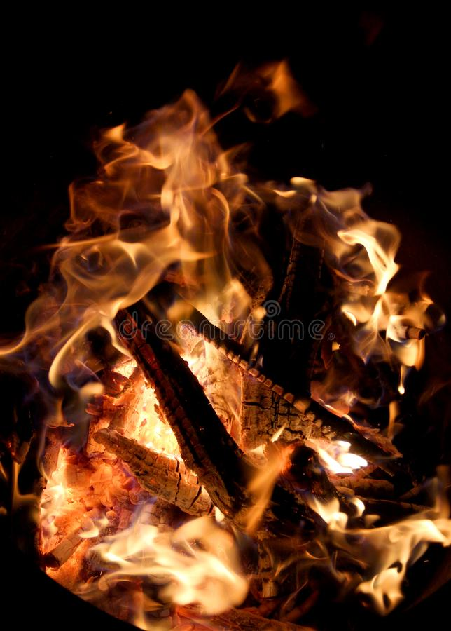 Charred and fire nine. Charred wood and bright flames on dark background royalty free stock photos