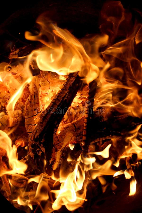 Charred and fire seven. Charred wood and bright flames on dark background stock photo