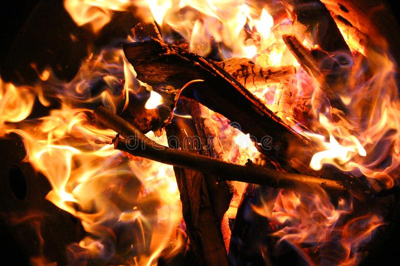Charred and fire two. Charred wood and bright flames on dark background royalty free stock photos