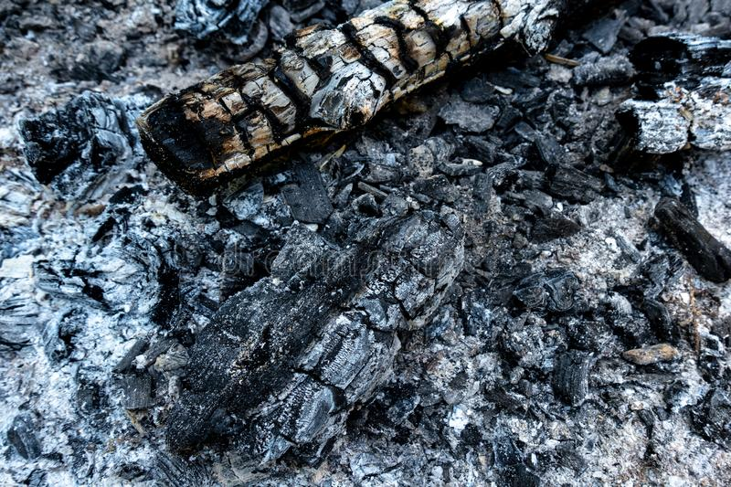 Charred wood and ash in closeup. Charred wood and ash in an extinguished fireplace in closeup stock photos