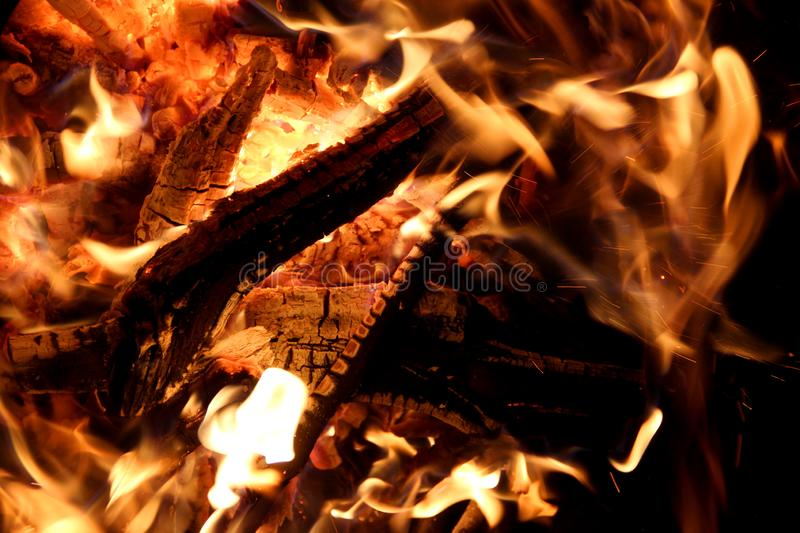 Charred and fire eight. Charred wood and bright flames on dark background royalty free stock image