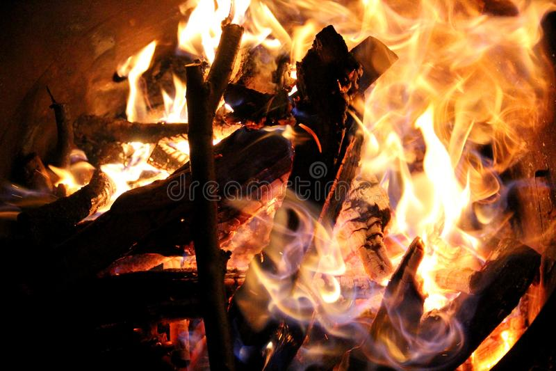 Charred and fire one. Charred wood and bright flames on dark background royalty free stock images