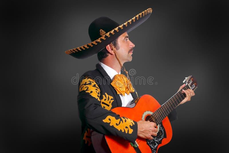 Charro Mariachi playing guitar on black stock photos