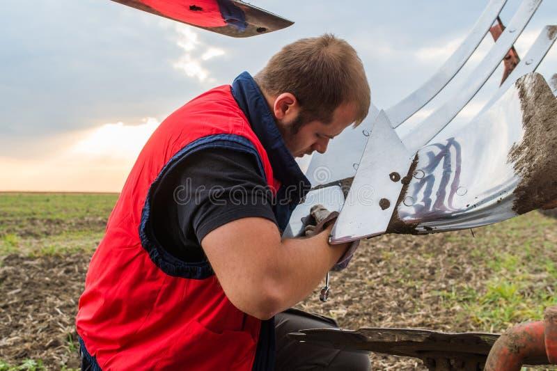 Charrue de fixation de mécanicien sur le tracteur photographie stock libre de droits