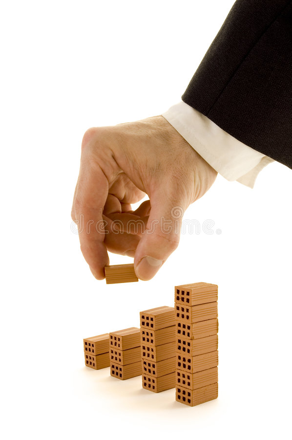 Chart of bricks. Businessman building a chart of bricks isolated on white royalty free stock image