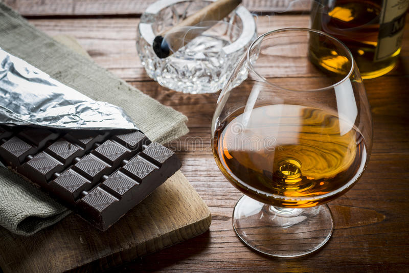 Charuto cubano e Chocolat do conhaque no fundo de madeira fotos de stock royalty free