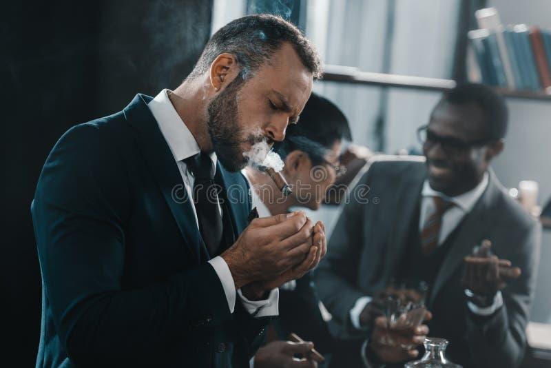 Charuto de fumo do homem de negócios com a equipe multicultural do negócio imagem de stock