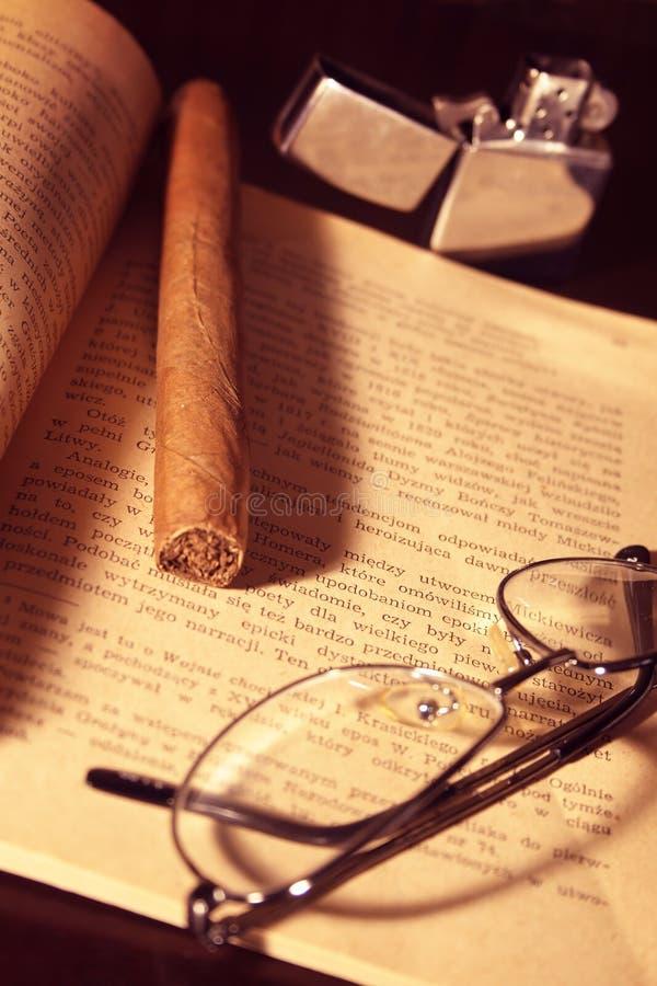 Charuto, isqueiro, vidros e livro fotografia de stock royalty free