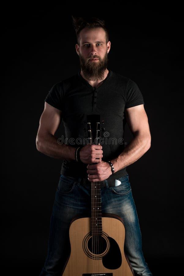 Charyzmatyczny i elegancki mężczyzna z brodą stoi długiego z gitarą akustyczną na czarnym odosobnionym tle zdjęcia stock