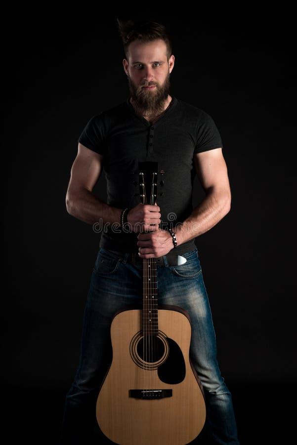 Charyzmatyczny i elegancki mężczyzna z brodą stoi długiego z gitarą akustyczną na czarnym odosobnionym tle fotografia stock