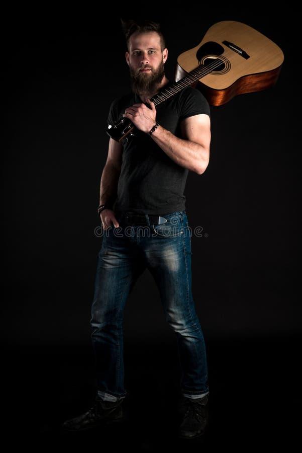 Charyzmatyczny i elegancki mężczyzna z brodą stoi długiego z gitarą akustyczną na czarnym odosobnionym tle zdjęcia royalty free