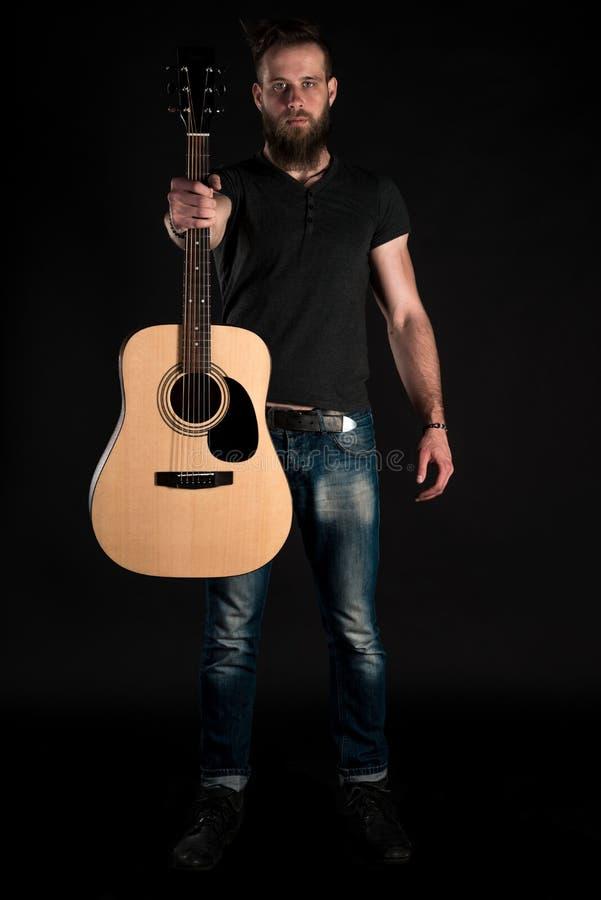 Charyzmatyczny i elegancki mężczyzna z brodą stoi długiego z gitarą akustyczną na czarnym odosobnionym tle fotografia royalty free