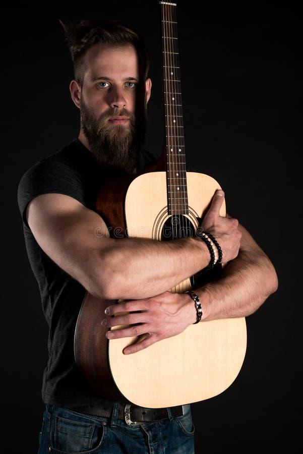 Charyzmatyczny i elegancki mężczyzna z brodą stoi długiego z gitarą akustyczną na czarnym odosobnionym tle zdjęcie royalty free