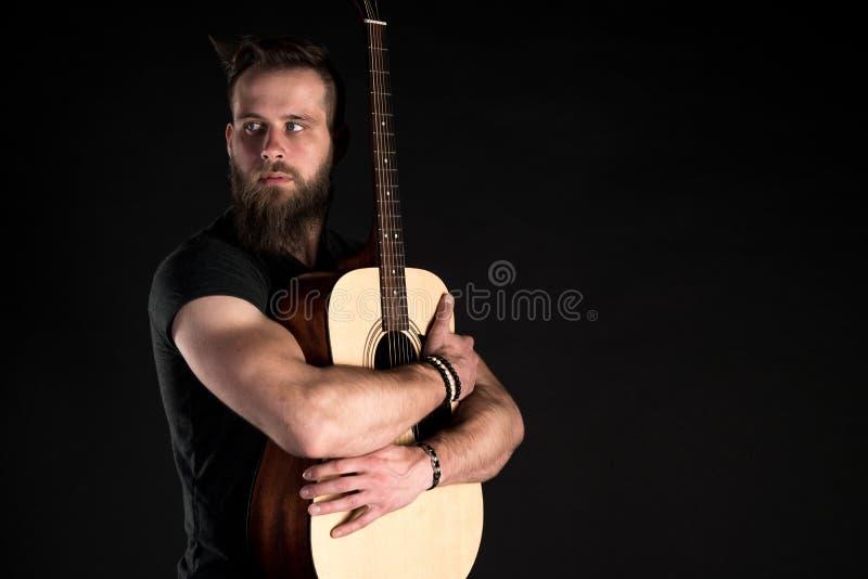 Charyzmatyczny i elegancki mężczyzna z brodą stoi długiego z gitarą akustyczną na czarnym odosobnionym tle obrazy stock