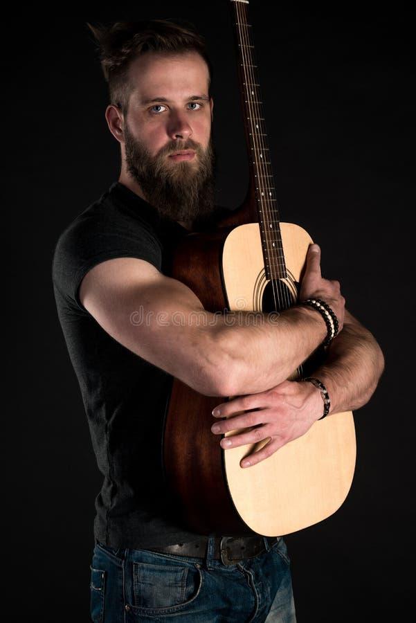 Charyzmatyczny i elegancki mężczyzna z brodą stoi długiego z gitarą akustyczną na czarnym odosobnionym tle obraz royalty free