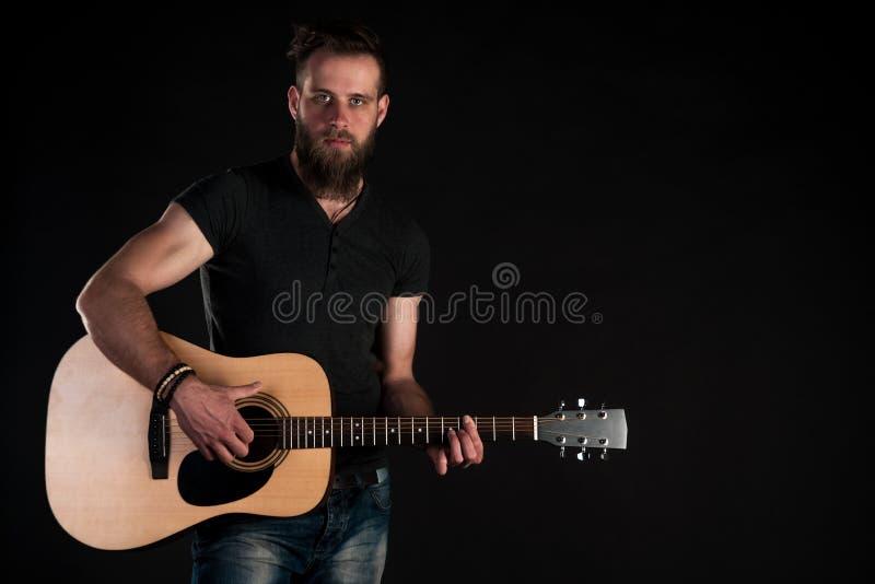 Charyzmatyczny i elegancki mężczyzna z brodą stoi długiego z gitarą akustyczną na czarnym odosobnionym tle obraz stock
