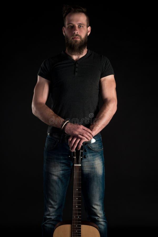 Charyzmatyczny i elegancki mężczyzna z brodą stoi długiego z gitarą akustyczną na czarnym odosobnionym tle Pionowo fra fotografia stock