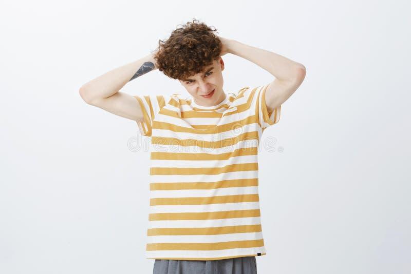 Charyzmatyczny i figlarnie młody europejczyka palu facet z kędzierzawą fryzurą w pasiastej koszulki grimacing skinieniu jako mien obrazy stock