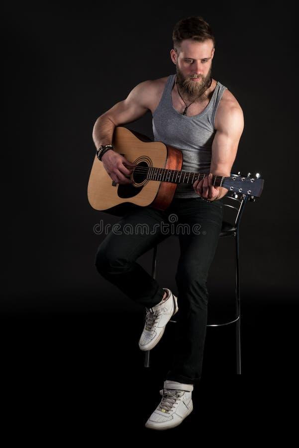 Charyzmatyczny mężczyzna z brodą, bawić się gitarę akustyczną na czarnym odosobnionym tle, Vertical rama zdjęcie stock